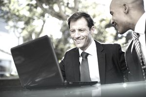 Businessmen using laptop outdoors