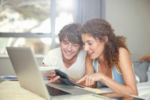 young-couple-budgeting-laptop-and-bed.jpg