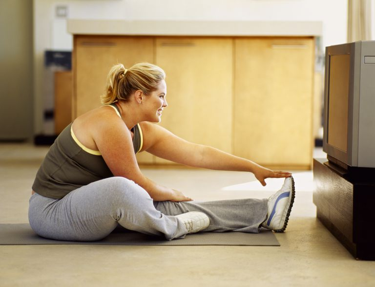 Woman stretching in front of her tv