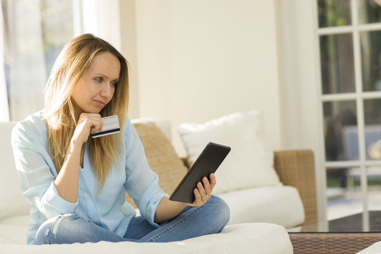 woman with credit card in hand looking at tablet