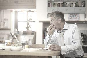 Man yawning at kitchen table