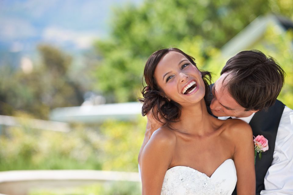 A groom kissing his new wife lovingly in the neck