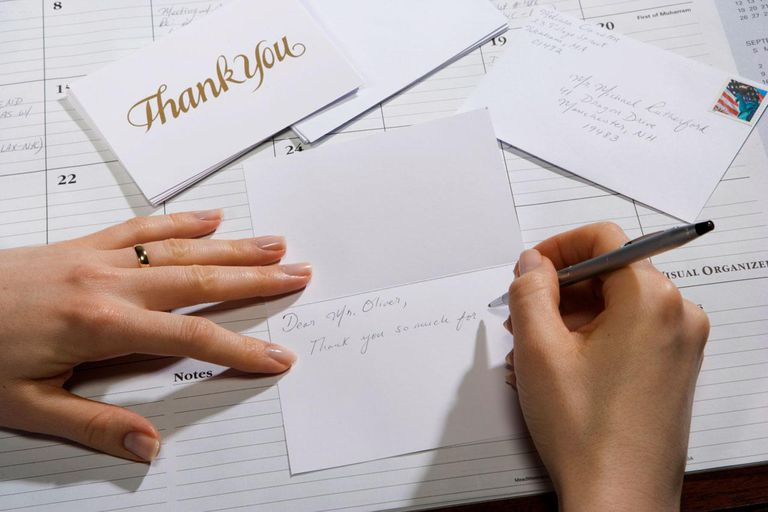 Woman writing greeting card, close-up of hands