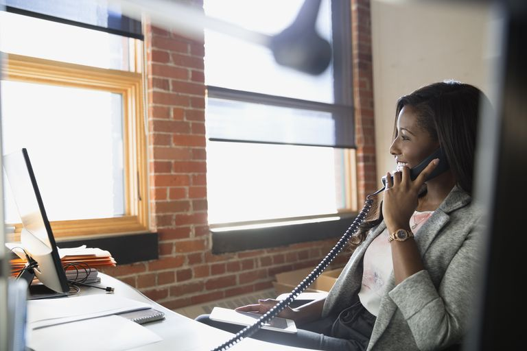 Businesswoman talking on telephone at office desk