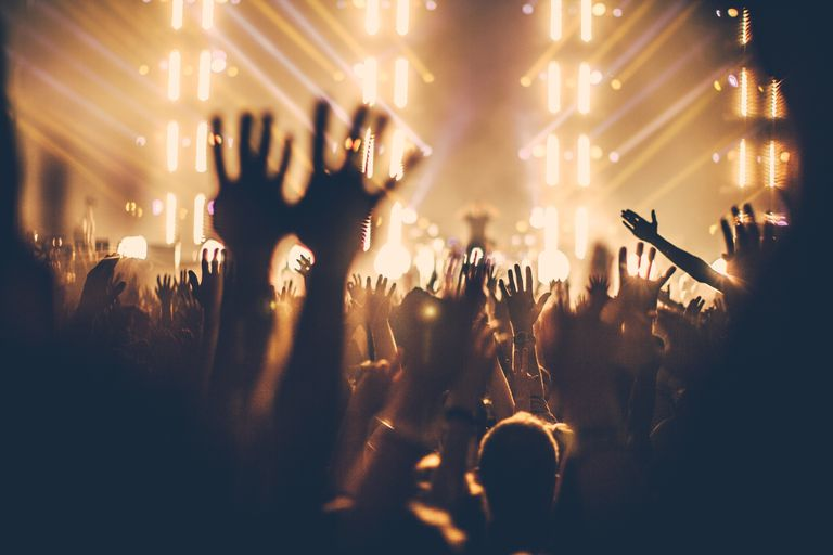 People Enjoying Music Concert With Hands Raised At Night