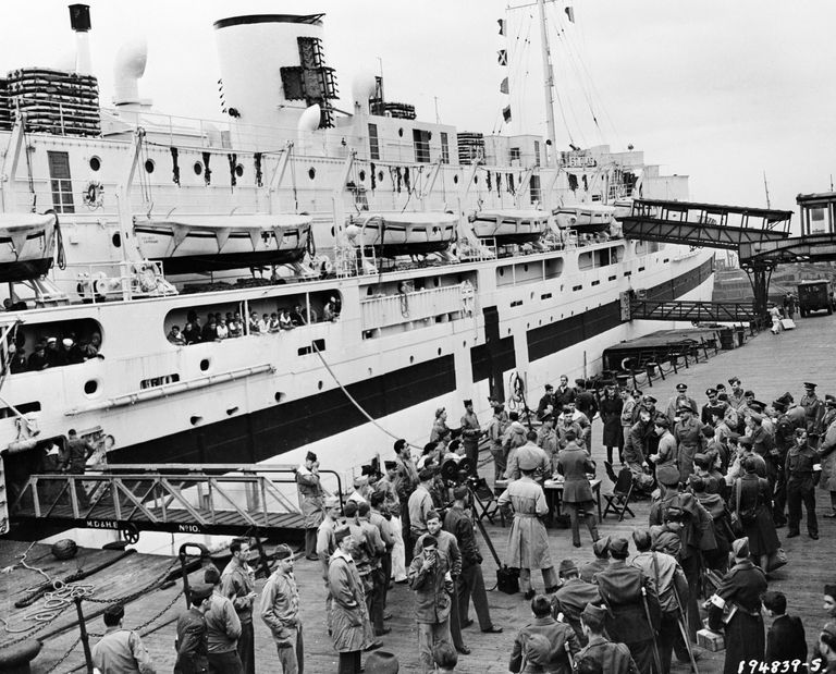 UK, Liverpool, Wounded GI's watch from decks of US Army hospital ship St Olaf as other GI's prepare to board ship at dock