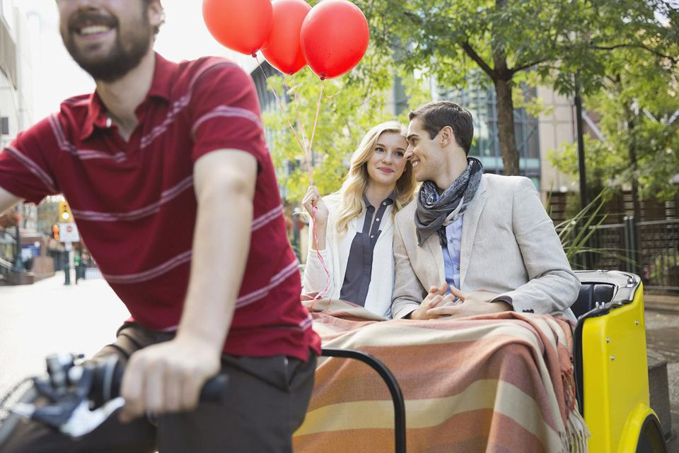 Couple with balloons riding in rickshaw