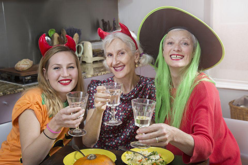 Dressed up women toast at halloween dinner.