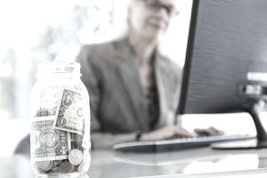Businesswoman working, jar of money in foreground