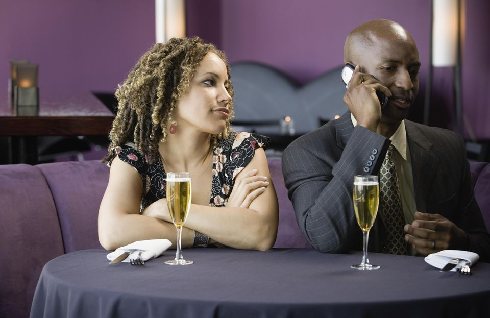 Man and woman sitting in restaurant, man talking on cell phone