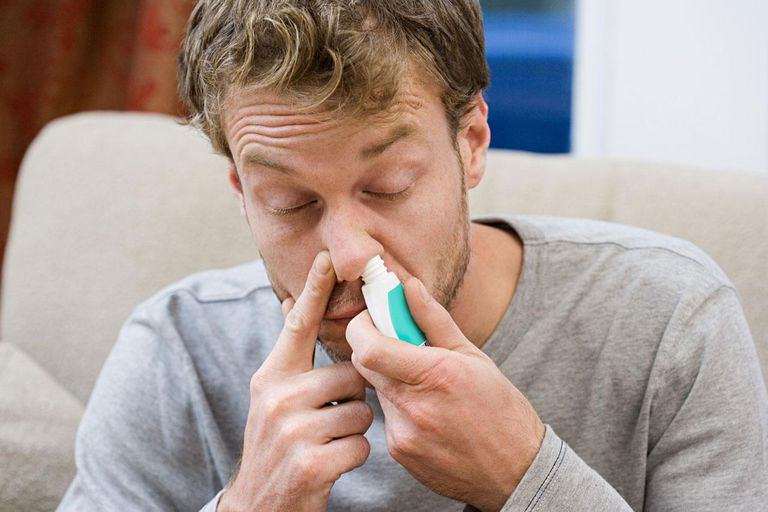 Man inhaling decongestant