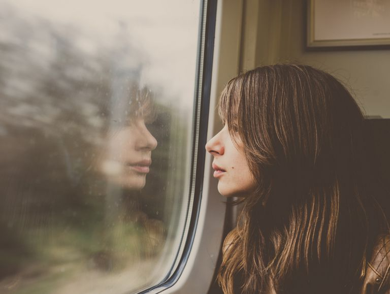 Woman looking through window in a train