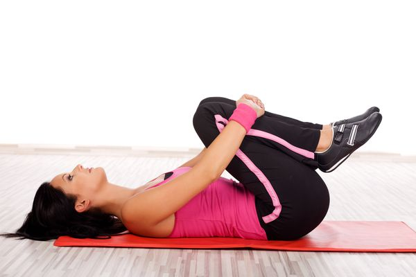 Woman does the double legged knees to chest stretch.
