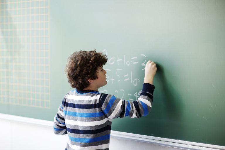 Boy writes math problems on chalkboard