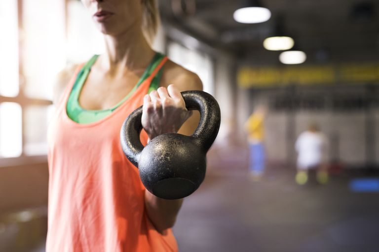 Unrecognizable young fit woman in gym working out, holding kettlebell