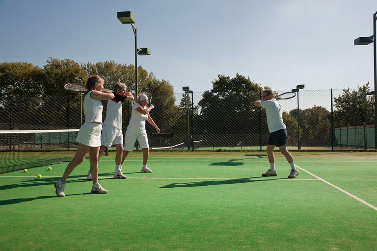 Senior and mature adults practising tennis