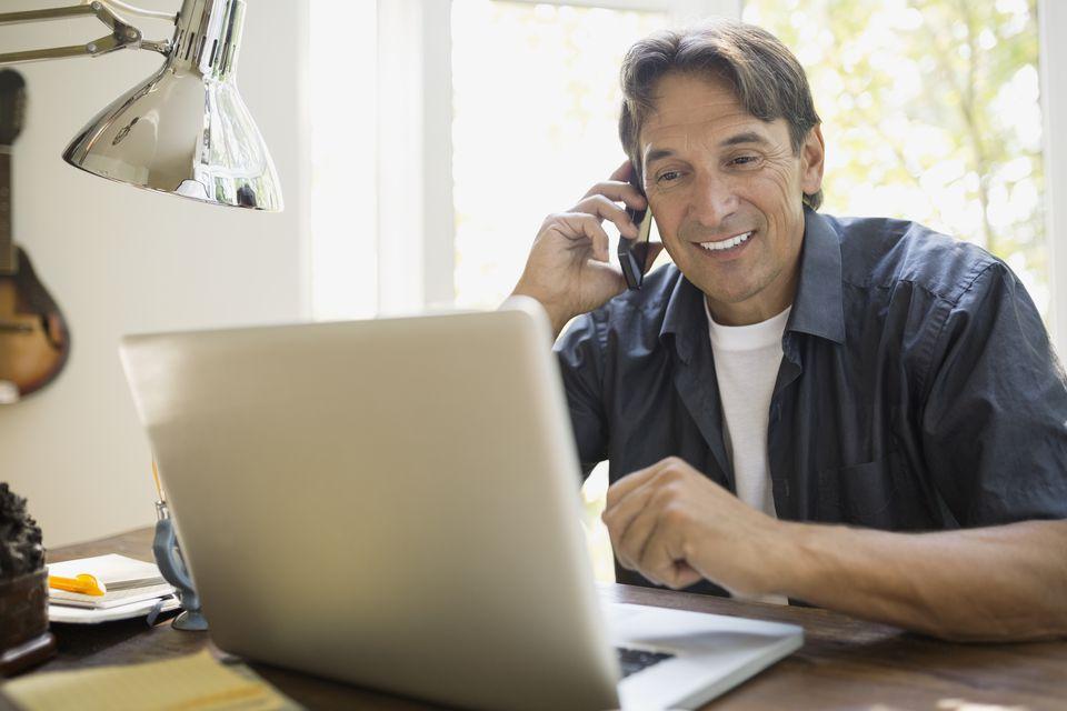 Man at laptop talking on cell phone
