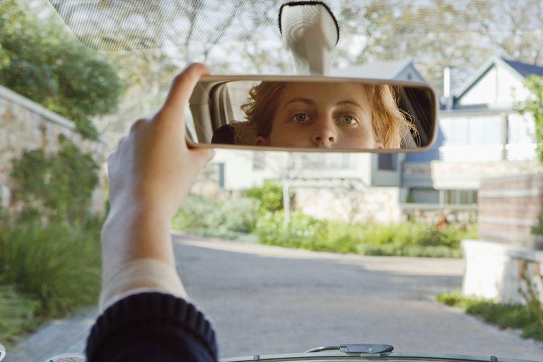 teen girl driver adjusting mirror in car