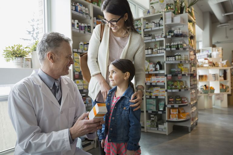 pharmacist giving mother a box of supplements