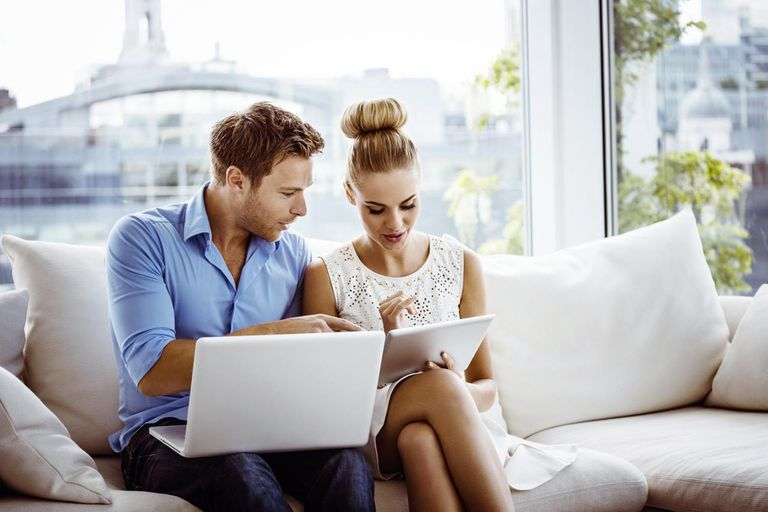 Young couple sitting on sofa in an apartment and using digital tablet and laptop together
