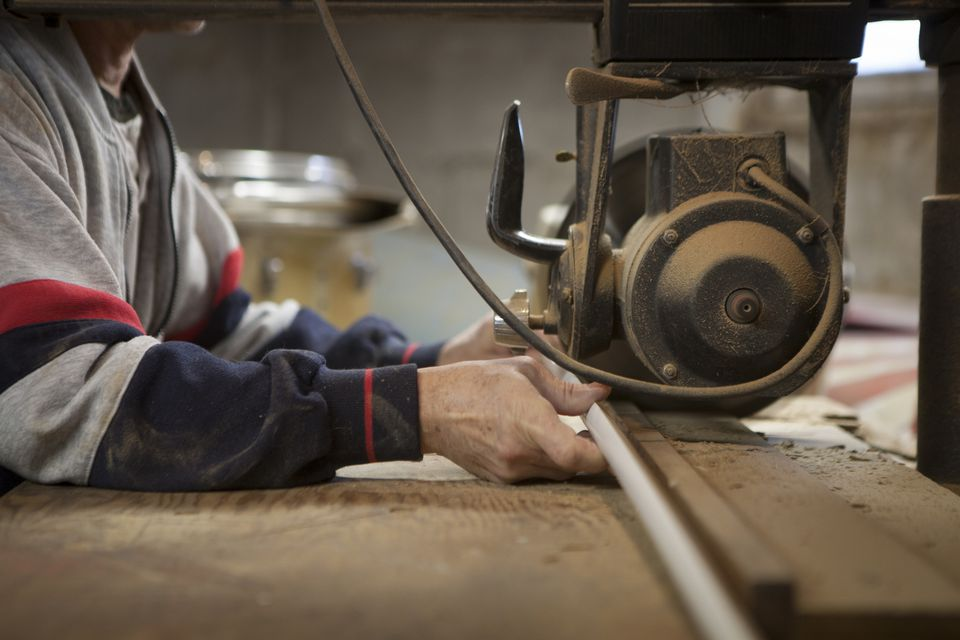 Close up of man using radial arm saw in workshop