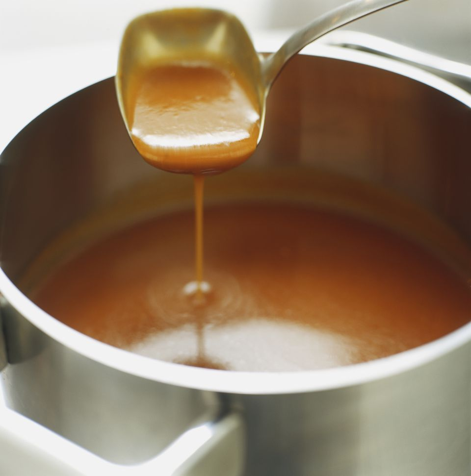 Brown sauce being ladled out of saucepan, close up