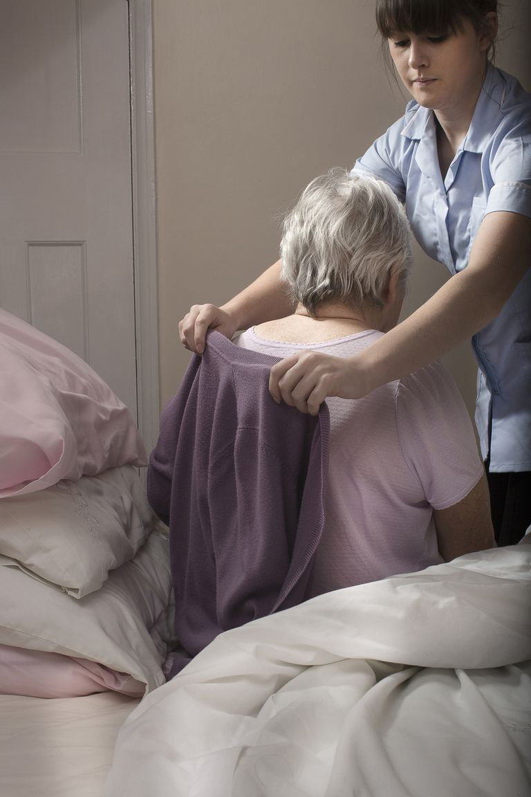 Personal care assistant helping senior woman to dress