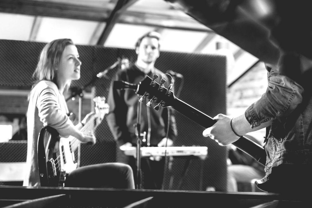 three band members rehearsing