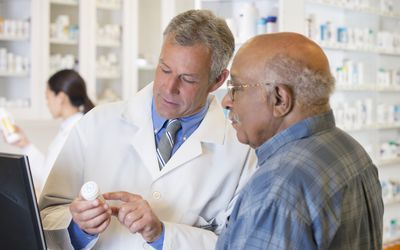 Elderly man talking with his pharmacist.