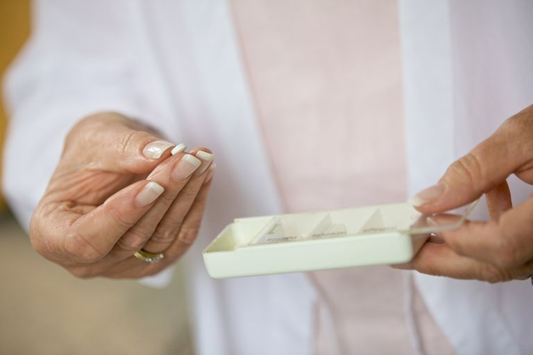 woman taking white pill out of pill organizer container