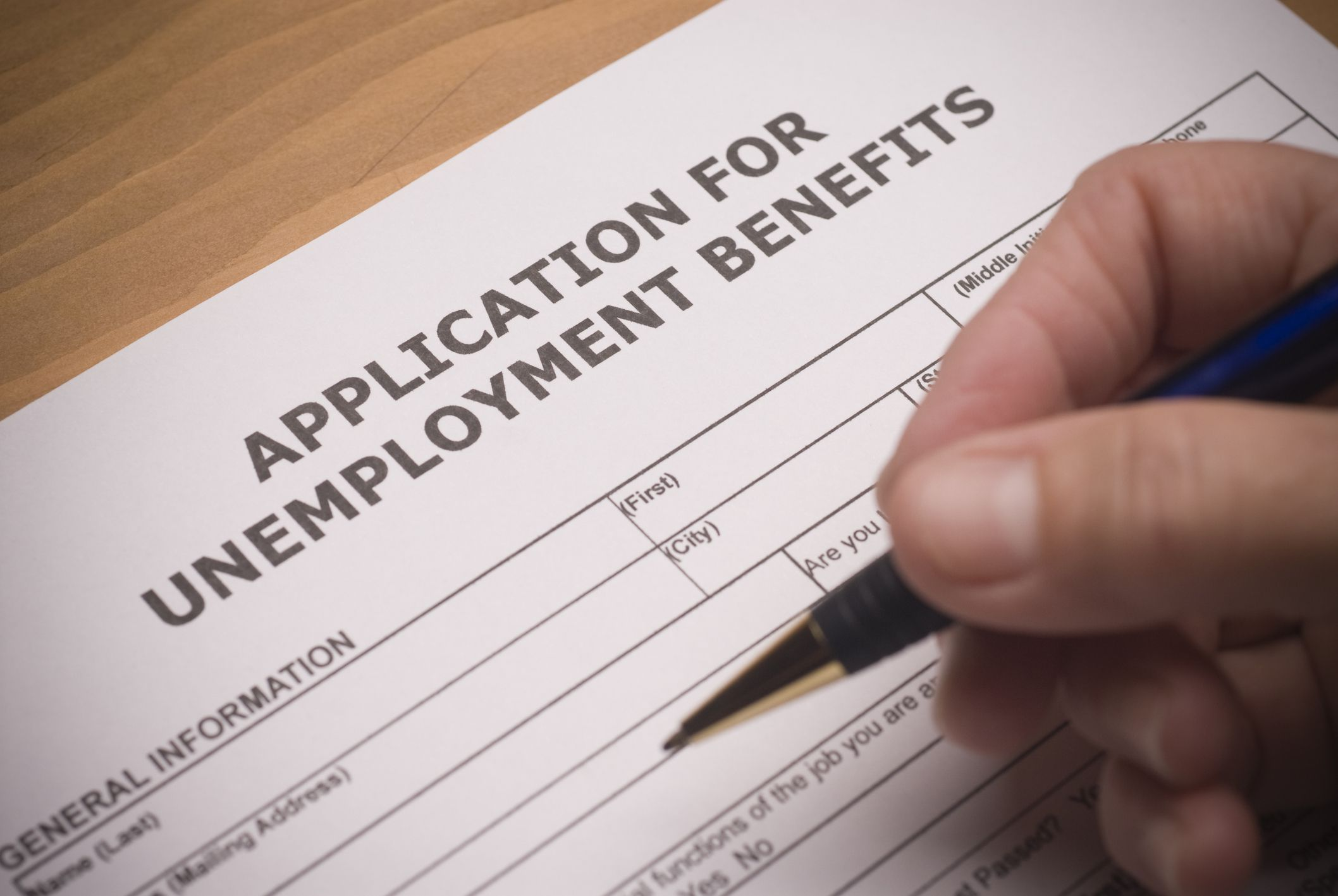 Applying for oklahoma unemployment benefits unemployment benefits form and hand holding pen xflitez Gallery