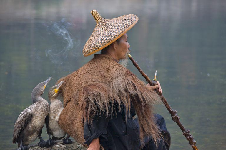 China, Guangxi Province, Yangshuo, fisherman wearing straw coat smoking a pipe