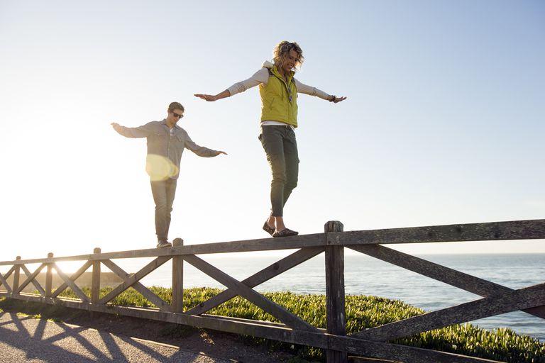 Adults balancing on fence