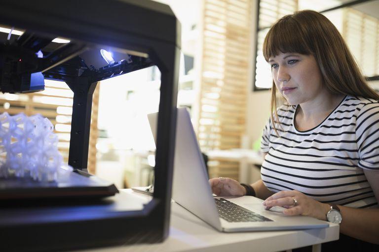 Female designer using laptop at 3D printer in office