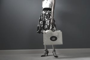 Woman standing with shopping bag, low section