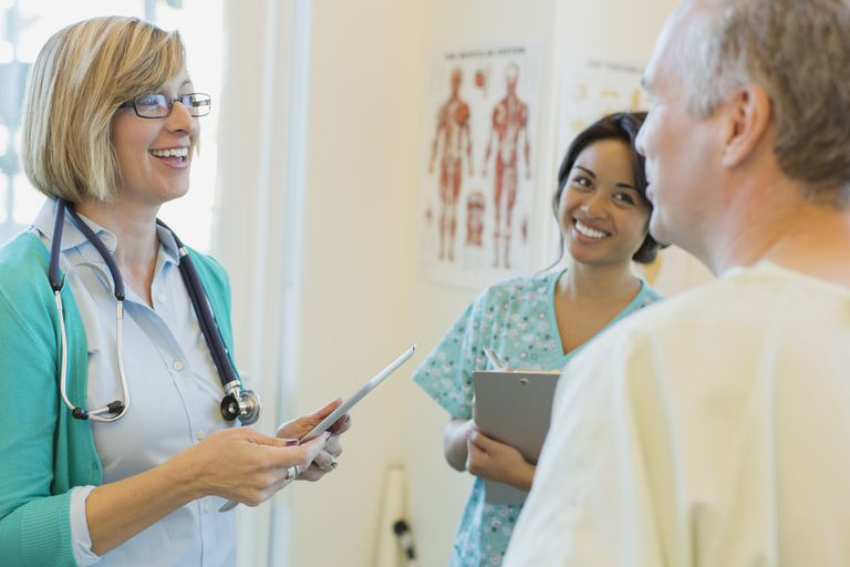 Happy female doctor and nurse discussing with male patient in clinic