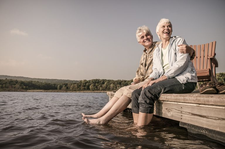 Older couple sitting on the edge of a dock, happy they found out about spousal benefits.