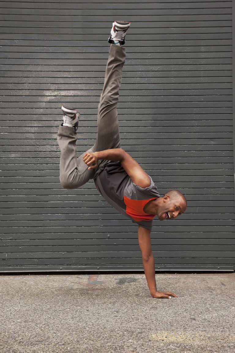 African American man break dancing on city sidewalk