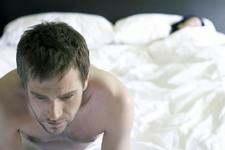 Young man sitting on bed, woman sleeping in background