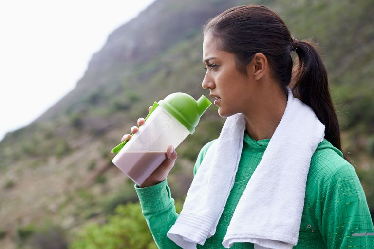 A young ethnic woman drinking a sports drink outdoors