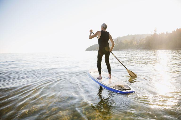 Senior man paddle boarding in ocean