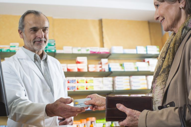 senior woman handing card to pharmacist