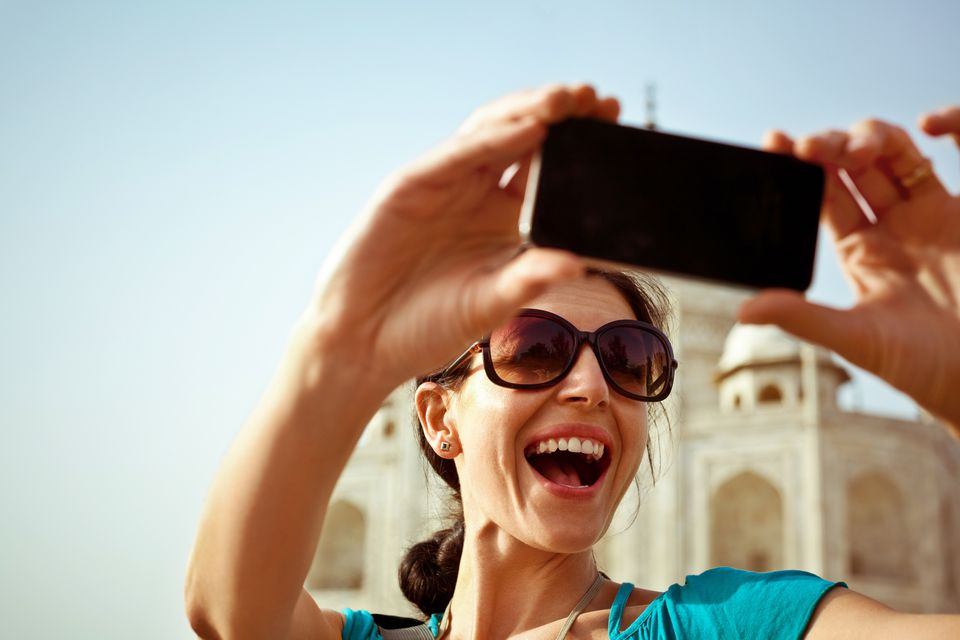 Foreign woman at the Taj Mahal taking a selfie.
