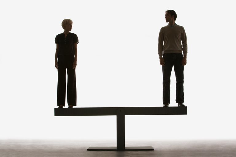 Two people standing on a balancing scale.