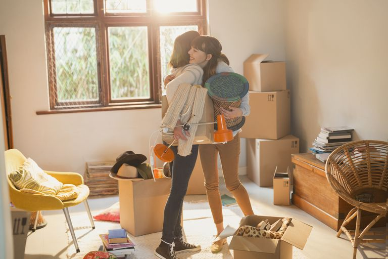 Mother and daughter hugging unpacking boxes in apartment