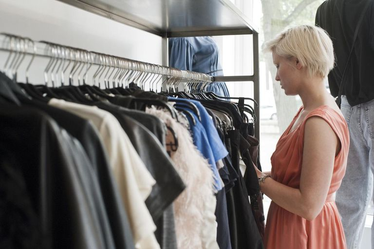 Woman looks at clothes in fashion store