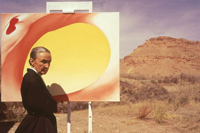 American artist Georgia O'Keeffe (1887 - 1986) poses outdoors beside an easel with a canvas from her series, 'Pelvis Series Red With Yellow,' Albuquerque, New Mexico, 1960