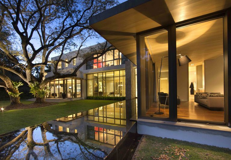 Modern House in Miami by Taylor & Taylor designed around trees and water, large windows, interior exterior