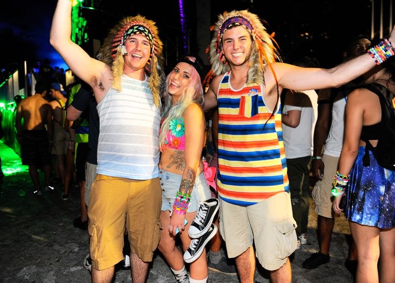 White partygoers at a music festival practice cultural appropriation by wearing feathered headdresses traditionally used in Native American ceremonies.