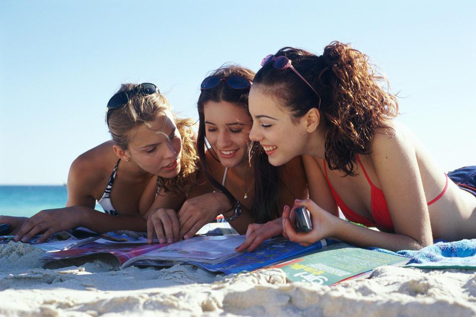 Three teenage girls (16-18) lying on beach talking over magazine